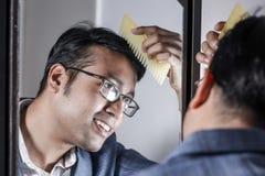 Asiatisk man i dräkt som framme sköter hans utseende av en spegelskönhet som utformar livsstil royaltyfri fotografi