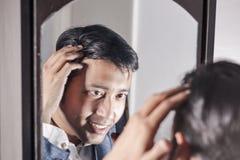 Asiatisk man i dräkt som framme sköter hans utseende av en spegelskönhet som utformar livsstil royaltyfri bild