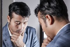 Asiatisk man i dräkt som framme sköter hans utseende av en spegelskönhet som utformar livsstil arkivfoto