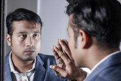 Asiatisk man i dräkt som framme sköter hans utseende av en spegelskönhet som utformar livsstil arkivfoton