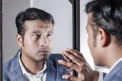 Asiatisk man i dräkt som framme sköter hans utseende av en spegelskönhet som utformar livsstil fotografering för bildbyråer