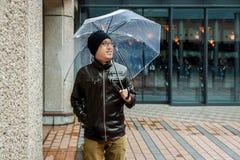 Asiatisk man i ett brunt omslag med ett klart paraply Fotografering för Bildbyråer