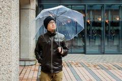 Asiatisk man i ett brunt omslag med ett klart paraply Arkivbilder