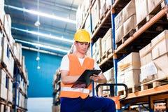Asiatisk man i kontrollerande lista för industriellt lager arkivbild