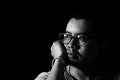 Asiatisk man i mörkret som ut ser fönstret Arkivfoto