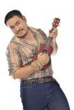 Asiatisk man i plädet som spelar ukulelet Arkivfoton