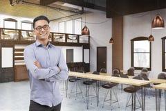 Asiatisk man i restaurang med långa tabeller Arkivbild