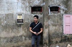 Asiatisk man i svart skjorta och mobiltelefon i handanseende på den gamla väggen fotografering för bildbyråer