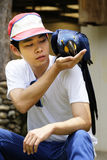 Asiatisk man med den härliga hyacintarapapegojan Arkivfoto