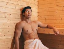 Asiatisk man med den muskulösa kroppen som kopplar av i bastu royaltyfria foton
