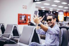 Asiatisk man med ryggsäckhandelsresanden som använder den smarta mobiltelefonen för den videopd appellen och tar på en flygplats arkivfoton