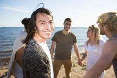 Asiatisk man med vänner på stranden royaltyfri fotografi