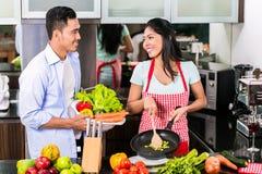 Asiatisk man och kvinna som tillsammans lagar mat Arkivbilder