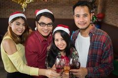 Asiatisk man- och kvinnakläderSanta Claus hatt och innehavchampagneexponeringsglas förestående i julparti Royaltyfri Bild
