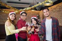 Asiatisk man- och kvinnakläderSanta Claus hatt och innehavchampagneexponeringsglas förestående i julparti Royaltyfri Fotografi
