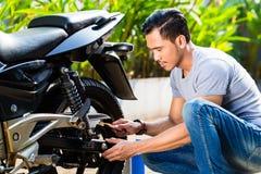 Asiatisk man på motorcykelunderhåll Fotografering för Bildbyråer