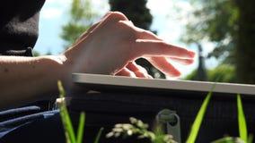 Asiatisk man` s fingrar maskinskrivning på bärbara datorn arkivfilmer