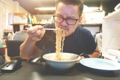 Asiatisk man som äter kryddiga ögonblickliga nudlar som mycket är varma och Fotografering för Bildbyråer
