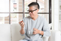 Asiatisk man som äter vitaminer Arkivfoton