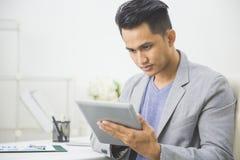 Asiatisk man som använder minnestavlaPC Royaltyfri Fotografi