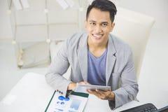 Asiatisk man som använder minnestavlaPC Royaltyfri Bild