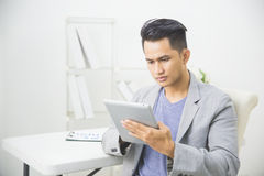 Asiatisk man som använder minnestavlaPC Fotografering för Bildbyråer