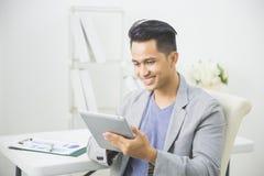 Asiatisk man som använder minnestavlaPC Arkivfoton