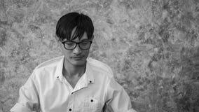 Asiatisk man som bara sitter i huset arkivfoton