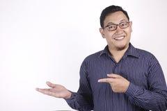 Asiatisk man som framlägger något på hans sida med kopieringsutrymme arkivfoto