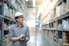 Asiatisk man som gör inventering, genom att använda minnestavlan i lager fotografering för bildbyråer