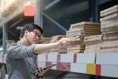 Asiatisk man som gör inventering, genom att använda minnestavlan i lager arkivbilder