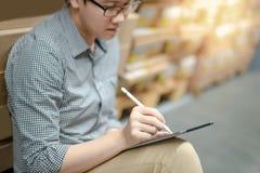 Asiatisk man som gör inventering, genom att använda minnestavlan i lager arkivfoto