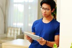 Asiatisk man som hemma använder minnestavladatoren Royaltyfri Foto