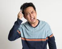 Asiatisk man som kammar hans tilltrasslade hår Arkivbild