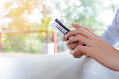 Asiatisk man som kopplar av med att rymma en telefon i hand, genom att använda smartphonen arkivfoto