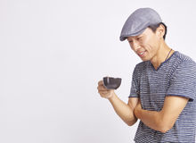 Asiatisk man som ler på koppen kaffe som isoleras på vit Royaltyfria Foton