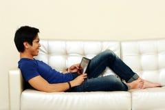 Asiatisk man som ligger på soffan med minnestavladatoren Royaltyfri Foto