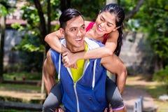 Asiatisk man som på ryggen bär hans flickvän för sport Fotografering för Bildbyråer