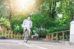 Asiatisk man som rider en cykel för avkoppling royaltyfria bilder
