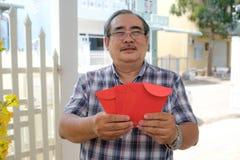 Asiatisk man som rymmer det röda kuvertet, mån- nytt år royaltyfri bild