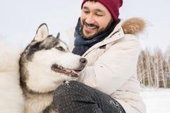 Asiatisk man som spelar med Husky Dog royaltyfria foton