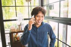 Asiatisk man som talar på smartphonen Arkivbild