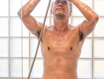 Asiatisk man som tar en dusch i badrummet royaltyfria bilder