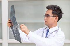 Asiatisk mandoktor som ser resultat för röntgenstråleCT-bildläsning Arkivfoton