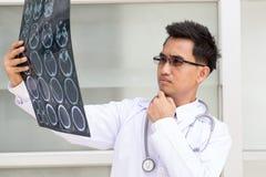 Asiatisk mandoktor som ser resultat för röntgenstråleCT-bildläsning Arkivbilder
