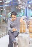 Asiatisk manhandelsresande som använder mobiltelefonen i flygplats, livsstil genom att använda mobiltelefonanslutningsbegrepp Arkivbild