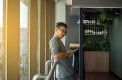 Asiatisk manhandelsresande som använder mobiltelefoninternet, och wifi i flygplats, livsstil genom att använda mobiltelefonanslut Royaltyfri Foto