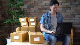 Asiatisk manlig affärsentreprenör som hemma använder bärbara datorn med packar av askar lager videofilmer