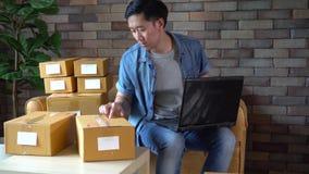 Asiatisk manlig affärsentreprenör som hemma använder bärbara datorn med packar av askar stock video