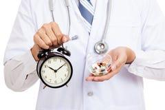 Asiatisk manlig doktorsshow en klocka och preventivpillerar arkivbilder